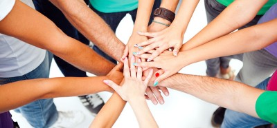 A group of people showing their unity by putting their hands one on top of the other.