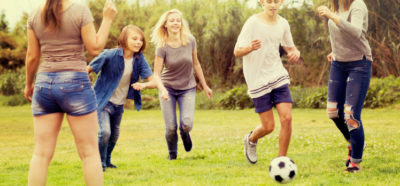 Group of carefree teenagers having fun and kicking football in park on summer day